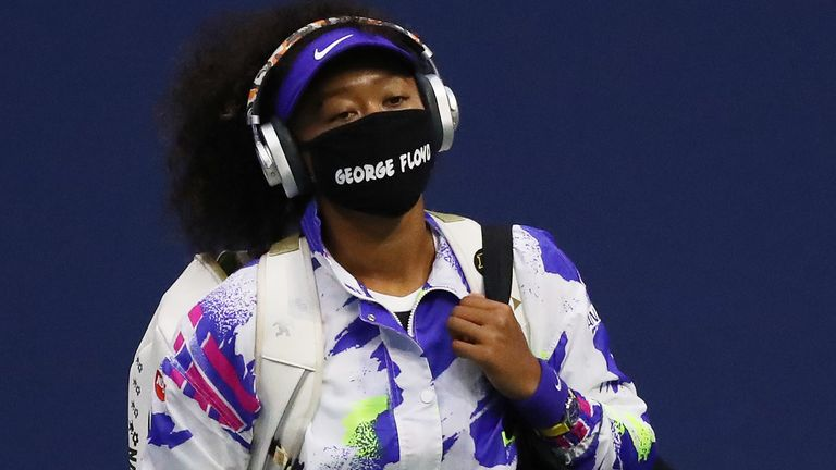 Naomi Osaka of Japan walks in wearing a mask with the name of George Floyd on it before her Women's Singles quarter-finals match against Shelby Rogers of the United States on Day Nine of the 2020 US Open at the USTA Billie Jean King National Tennis Center on September 8, 2020 in the Queens borough of New York City.