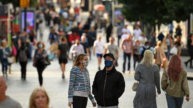A couple wearing protective face coverings chat in the street in Liverpool city centre, north-west England on September 18, 2020 after the British government imposed fresh restrictions on the city after an rise in cases of the novel coronavirus. - Millions more people in northern and central England faced new restrictions over a surge in coronavirus cases, the British government announced on Friday, as it warned another national lockdown could be imminent. Tighter regulations preventing people from socialising with anyone outside their household will come into force from next Tuesday across parts of the northwest, the Midlands and West Yorkshire. Food and drink venues in the northwestern areas of Merseyside, Warrington, Halton and Lancashire will be restricted to table service only, while pubs and bars will have to shut early by 10:00 pm (2100 GMT). (Photo by Oli SCARFF / AFP) (Photo by OLI SCARFF/AFP via Getty Images)