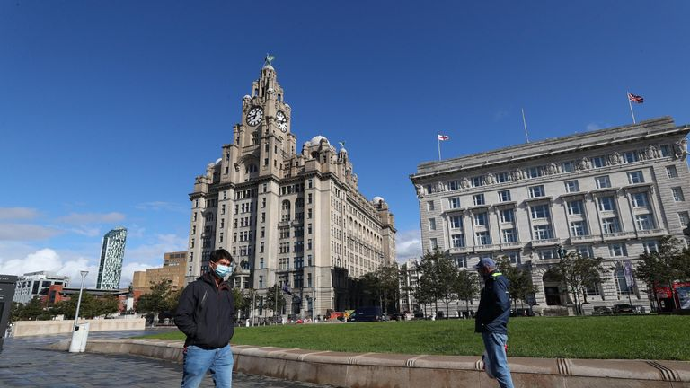 A man in a face mask walks past the Liver Building in Liverpool. New coronavirus restrictions in Liverpool, Warrington, Hartlepool and Middlesbrough will come into force on Saturday morning at one minute past midnight, Downing Street has said.