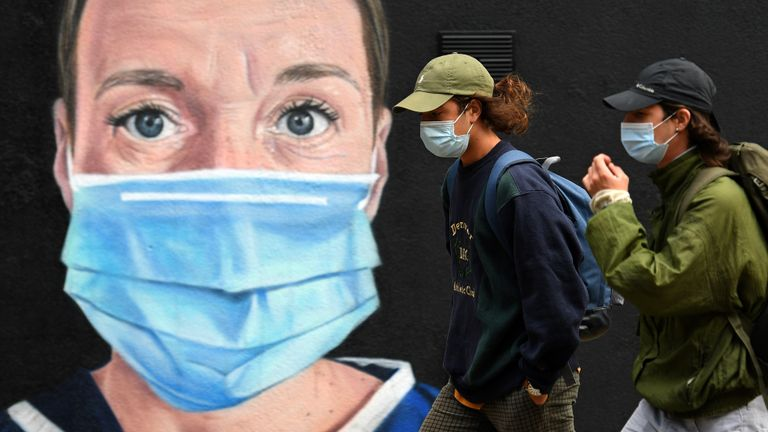 "Pedestrians wearing a face mask or covering due to the COVID-19 pandemic, walk past graffiti by the artist @akse_p19, depicting a nurse in scrubs and a face mask, but with an Angel's halo above her head, in Manchester, northwest England on August 3, 2020. - Britain's ""Eat out to Help out"" scheme began Monday, introduced last month by Chancellor Rishi Sunak to help boost the economy claw its way from a historic decline sparked by the coronavirus crisis. (Photo by Oli SCARFF / AFP) / RESTRICTED TO EDITORIAL USE - MANDATORY MENTION OF THE ARTIST UPON PUBLICATION - TO ILLUSTRATE THE EVENT AS SPECIFIED IN THE CAPTION (Photo by OLI SCARFF/AFP via Getty Images)"