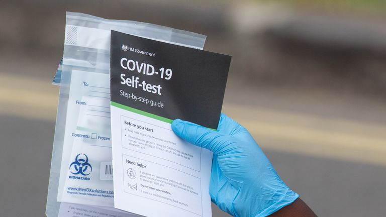Staff hand out self test kits at a Coronavirus testing centre in Southwark, London.