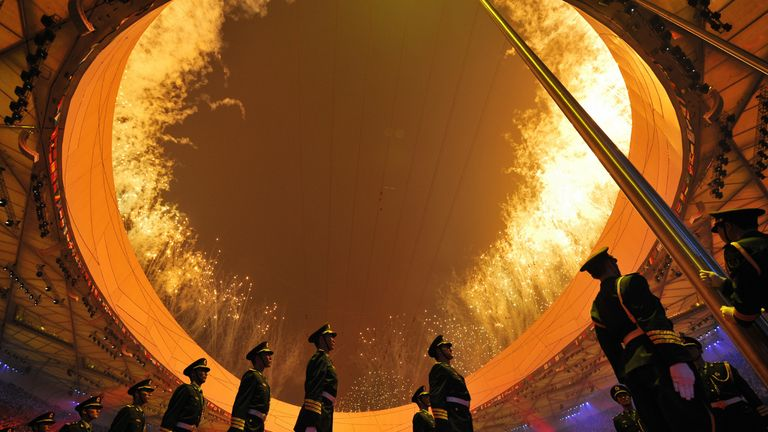 """Chinese solidiers wait for the flag raising ceremony as fireworks go off during the opening ceremony of the 2008 Beijing Olympic Games in Beijing on August 8, 2008. The three-hour show at Beijing's iconic """"Bird's Nest"""" national stadium is set to see more than 15,000 performers showcase the nation's ancient history and its rise as a modern power.  AFP PHOTO / FABRICE COFFRINI (Photo credit should read FABRICE COFFRINI/AFP via Getty Images)"""