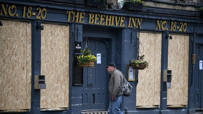 EDINBURGH, SCOTLAND - MARCH 26: A man walks past a boarded up pub in the Grassmarket as people are asked to socially distance themselves amid the coronavirus outbreak on March 26, 2020 in Edinburgh, Scotland. First Minister of Scotland Nicola Sturgeon along with British Prime Minister, Boris Johnson, implemented strict lockdown measures urging people to stay at home and only leave the house for basic food shopping, exercise once a day and essential travel to and from work.The Coronavirus (COVID-19) pandemic has spread to at least 194 countries, claiming over 21,000 lives and infecting over 470,000 people. There have now been over 9,500 diagnosed cases in the UK and 463 deaths. (Photo by Jeff J Mitchell/Getty Images)