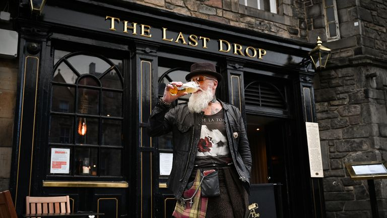 EDINBURGH, SCOTLAND - OCTOBER 07: Charles Douglas Barr enjoys a pint outside The Las Drop pub in the Grassmarket on October 7, 2020 in Edinburgh, Scotland. New restrictions aimed at slowing a surge in coronavirus cases are to be announced by Scotland's first minister Nicola Sturgeon. (Photo by Jeff J Mitchell/Getty Images)