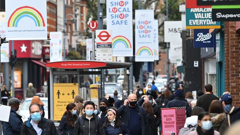Mask-wearing pedestrians are seen waking through west London