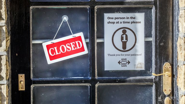 A closed sign next to a social distancing sign in a shop window in Haworth, West Yorkshire.
