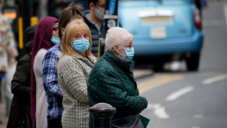 "MANCHESTER, ENGLAND - OCTOBER 15: People wear Covid-19 protection face masks as they walk through the city centre on October 15, 2020 in Manchester, England. Manchester was placed in the second of three alert levels this week when the British government introduced a new system for assessing covid-19 risk. However, the Manchester area fears it may be moved into tier 3 ""High Alert as it has reported some of the highest numbers of new cases per 100,000 residents. (Photo by Christopher Furlong/Getty Images)"