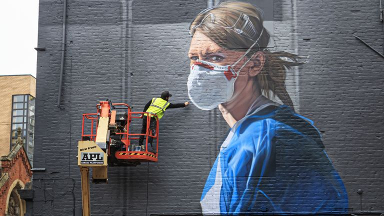 Artist Peter Barber works on a mural in Manchester city centre, depicting nurse Melanie Senior, after The National Portrait Gallery commissioned the mural based on a photograph by Johannah Churchill.