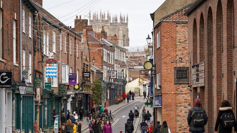 YORK, ENGLAND - OCTOBER 18: Visitors walk through the centre of York on October 18, 2020 in York, England. York city has become another of England's high risk areas placed under 'Tier 2' coronavirus lockdown measures as Government data indicates the R number range for the whole of the UK had increased slightly from between 1.2 and 1.5 last week to 1.3 and 1.5. Most notably the change will introduce a ban on people from different households from mixing anywhere indoors, prompting particular concern within the already badly-affected hospitality industry. (Photo by Ian Forsyth/Getty Images)