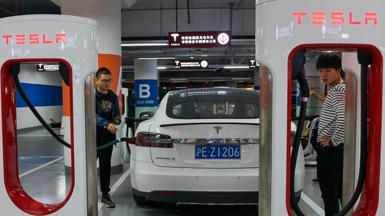 People charge their Tesla vehicles at a charging station inside a mall in Shanghai on October 23, 2017. - Tesla has reached an agreement with Shanghai authorities that would make it the first foreign automaker to build its own plant in China, putting it in the driver's seat in the world's biggest electric-vehicle market, the Wall Street Journal reported. (Photo by CHANDAN KHANNA / AFP)        (Photo credit should read CHANDAN KHANNA/AFP via Getty Images)