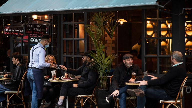 "LONDON, ENGLAND - OCTOBER 13: Customers sit outside a restaurant/cafe bar in Soho on October 13, 2020 in London, England. London Mayor Sadiq Khan said today that the city would move into Tier 2 of the government's new Covid-19 risk classification once it hits 100 new daily cases per 100,000 people, which could happen this week. The second or ""high"" tier of the three-tier system triggers a ban on household mixing, although pubs would remain open. (Photo by Dan Kitwood/Getty Images)"