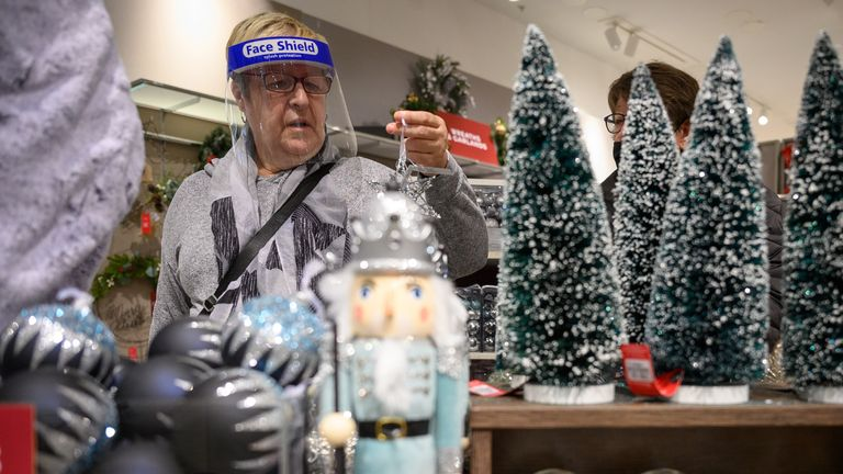 "LONDON, ENGLAND - OCTOBER 20: A customer browses some of the festive items in the Christmas gift and decoration section in the branch of retailer Marks and Spencer at Westfield White City on October 20, 2020 in London, England. The high street store has announced that searches for Christmas-related items have tripled on previous years. The British Retail Consortium (BRC) has launched a new ""Shop early, Start wrapping, Enjoy Christmas"" national campaign, encouraging British consumers to start their festive shopping early. The aim is to both spread the amount of footfall in stores to aid social distancing, and to ensure that retail stores survive the Christmas period, despite COVID-19 preventative measures. (Photo by Leon Neal/Getty Images)"