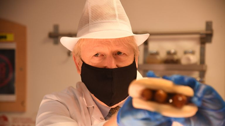 Prime Minister Boris Johnson holds up a roll filled with sausage during a visit to Royal Berkshire Hospital, Reading, to mark the publication of a new review into hospital food.