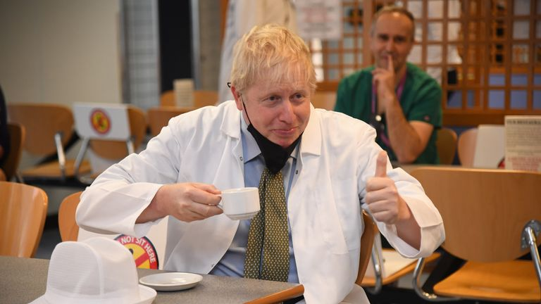 Prime Minister Boris Johnson (centre) has a drink in the canteen during a visit to Royal Berkshire Hospital, Reading, to mark the publication of a new review into hospital food.