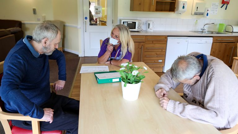 Care worker Cath Roe talks to residents William Buxton and Neil Fox on her rounds at Ashwood Court residential care home in Lowton, Warrington, as it reopens to visitors for the first time since lockdown began in March.