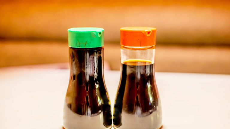 Two soy sauce bottles on the table.   One is considered low sodium and has a green top, the other is considered high (or normal) sodium which has a red top.