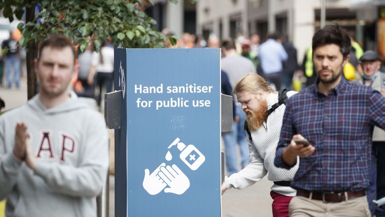 A man uses a public hand sanitiser in Leeds city centre, West Yorkshire, where tougher lockdown measures may be introduced locally after a rise in coronavirus infections.