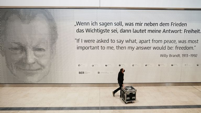An employee walks inside the terminal 1 of the Berlin-Brandenburg Willy-Brandt international Airport (BER) past a picture of former German chancellor Willy Brandt in Schoenefeld near Berlin on October 27, 2020. - Nine years late and eye-wateringly over budget, the Berlin region's new international airport will finally open on October 31, 2020 -- in the middle of a global pandemic that has crippled air travel. (Photo by Michael Kappeler / POOL / AFP) (Photo by MICHAEL KAPPELER/POOL/AFP via Getty Images)