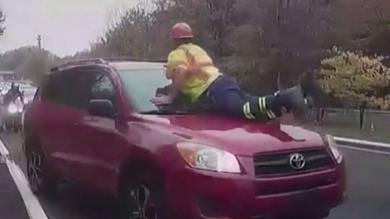 The New York State Department of Transportation has shared footage of a driver continuing down the road with a worker on the hood.