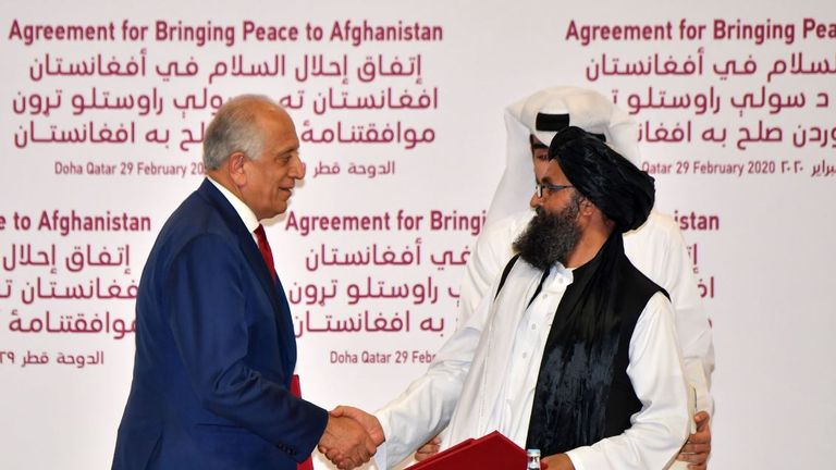 US Special Representative for Afghanistan Reconciliation Zalmay Khalilzad and Taliban co-founder Mullah Abdul Ghani Baradar shake hands after signing a peace agreement in February