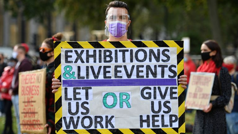 Workers from the arts, events and entertainments industries, many wearing face masks or coverings due to the COVID-19 pandemic, demonstrate against the lack of support, and continued restrictions placed upon their sectors during the coronavirus pandemic, during a protest in Parliament Square central London on September 29, 2020. - Britain's government has allowed some venues to partially reopen but many nightspots, particularly older theatres, remain closed because of strict social distancing ru