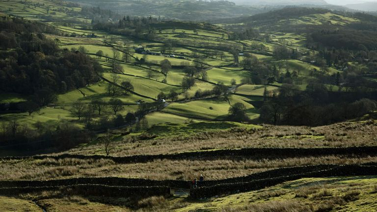 BRITAIN-LANDSCAPE-LAKE-DISTRICT Walkers admire the scenery as they negotiate a track on Wansfell, a hill in the Lake District National Park, near the town of Ambleside, northern England on November 24, 2017. / AFP PHOTO / OLI SCARFF (Photo credit should read OLI SCARFF/AFP via Getty Images)