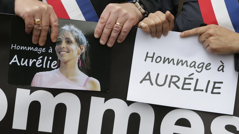 People holding a picture of Aurelie Chatelain at a event held in her memory in 2015