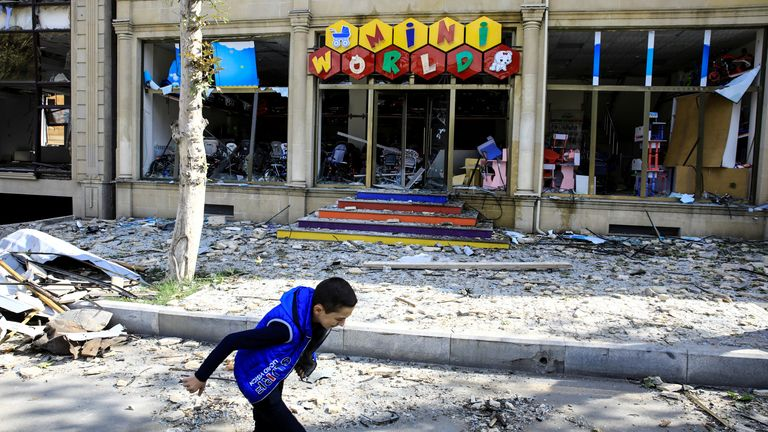 A boy runs past a damaged store after claims of a rocket attack on Ganja