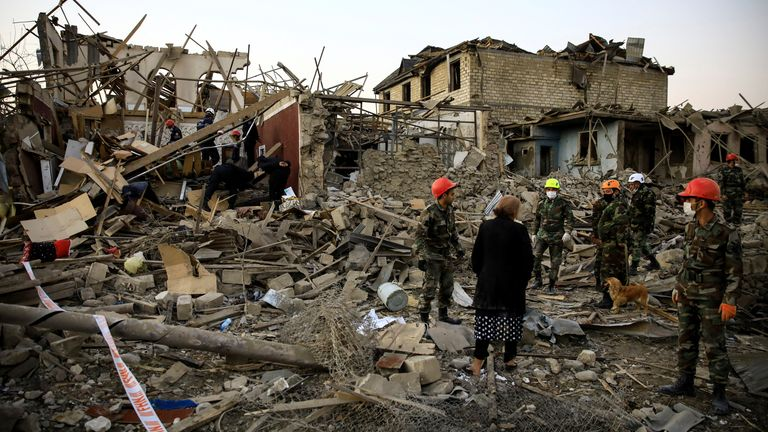 Search and rescue teams work on a blast site hit by a rocket in the city of Ganja, Azerbaijan