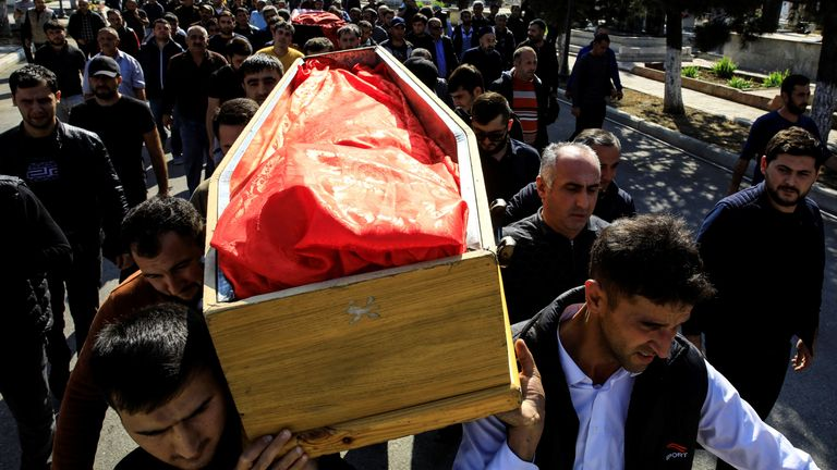 Relatives  carry the coffins of victims of a rocket attack during their funeral in the city of Ganja, Azerbaijan