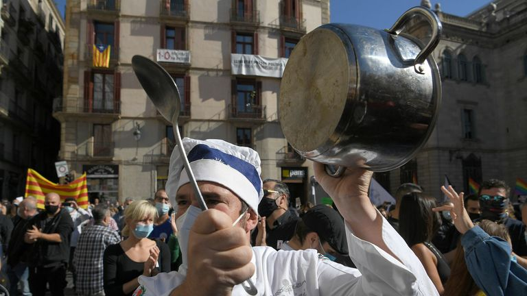 A cook bangs a pot during a demonstration against new restrictions in Barcelona