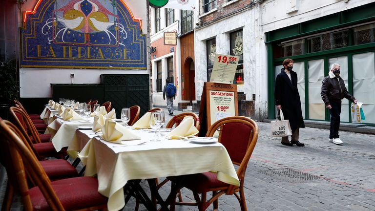 People walk past empty restaurant tables in Brussels