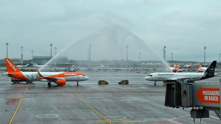 "Fire engines spray water to greet planes of airlines Lufthansa (R) and Easyjet, the first ones to arrive at Berlin's airport ""Berlin Brandenburg Airport Willy Brandt"", during the opening ceremony, in Schoenefeld, southeast of Berlin, on October 31, 2020. - Passenger flights are to begin landing on October 31, 2020 at Berlin's new international airport, a moment many Germans thought they might never see after years of embarrassing delays and spiralling costs. Pic: Getty"
