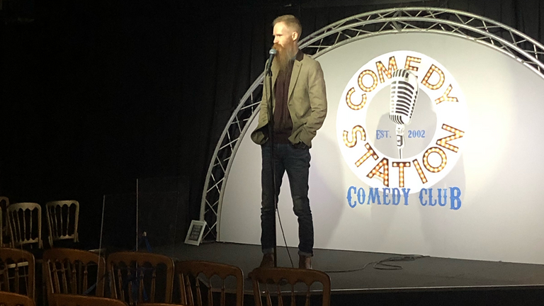 Ryan Gleeson, on stage at the comedy club he runs with his wife, Jen, says 'it's very, very stressful at the moment'