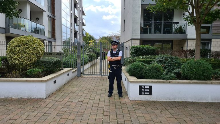 A policeman stands guard outside a block of flats on Clayponds road