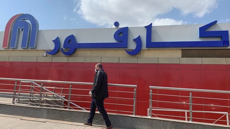 A man wearing a protective face mask walks outside a Carrefour hypermarket while Egypt ramps up its efforts to slow the spread the coronavirus disease (COVID-19) in Cairo, Egypt March 19, 2020. REUTERS/Amr Abdallah Dalsh