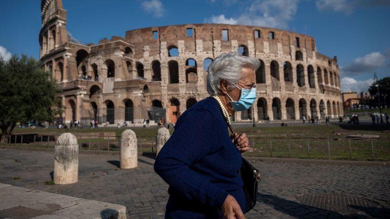 An elderly woman wears a mask as she walks near the Colosseum in Italy