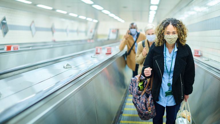 Mask-wearing commuter are seen travelling safely on the London Underground