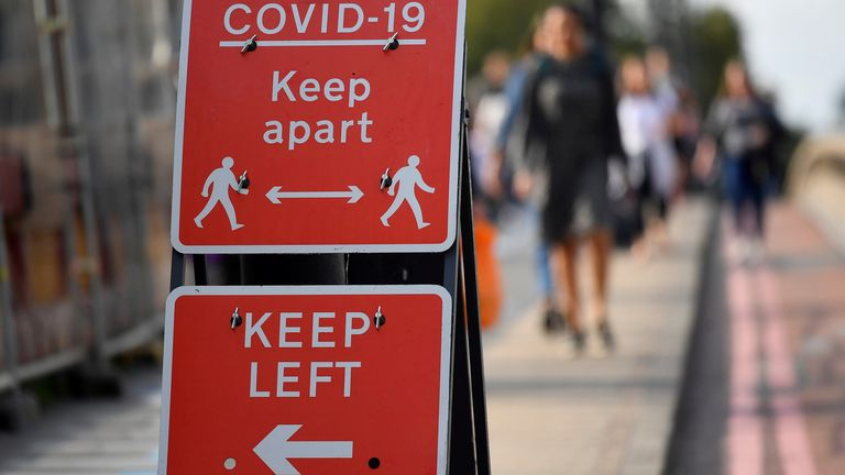 Pedestrians walk near public health signs