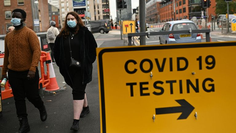 Pedestrians wearing protective face coverings walk past a Covid-19 testing sign in Manchester in north-west England on October 17, 2020, as further restrictions come into force as the number of novel coronavirus COVID-19 cases rises. - About 28 million people in England, more than half the population, are now living under tough restrictions imposed on Saturday as the country battles a surge in coronavirus cases. (Photo by Oli SCARFF / AFP) (Photo by OLI SCARFF/AFP via Getty Images)