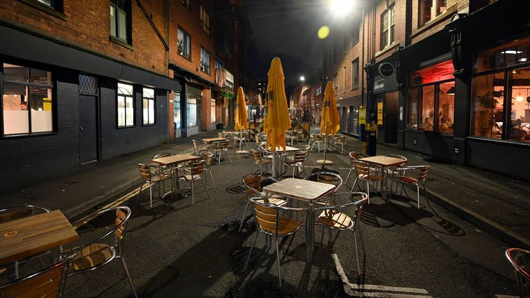 Empty tables and chairs at an outdoor eating area in the city centre of Manchester