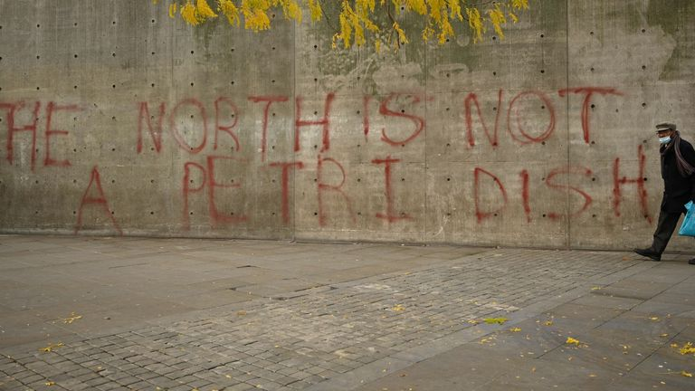 A man wearing a face-mask walks past graffiti in central Manchester
