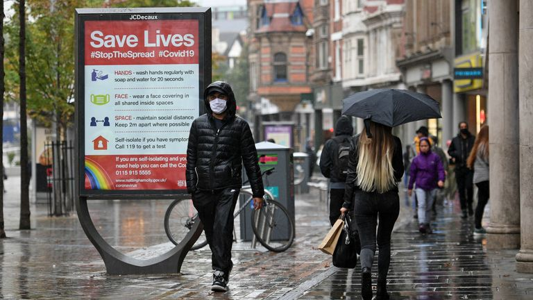 A mask-wearing man walks through Nottingham as the country has reached a 'tipping point' in relation to coronavirus