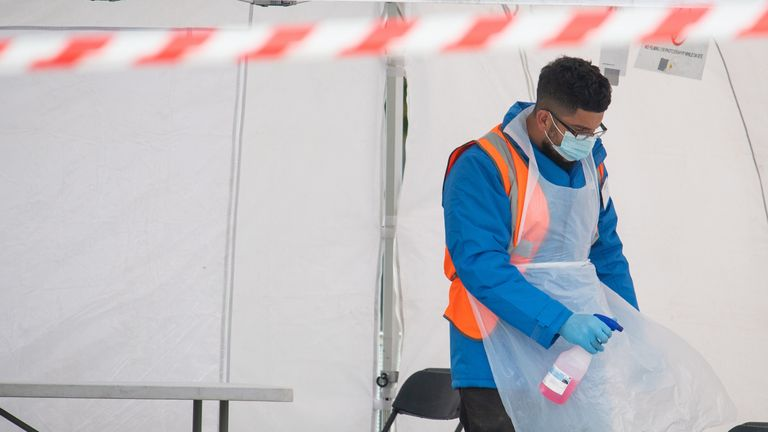 A member of staff disinfects tables between tests at a walk in COVID-19 testing centre in Southwark