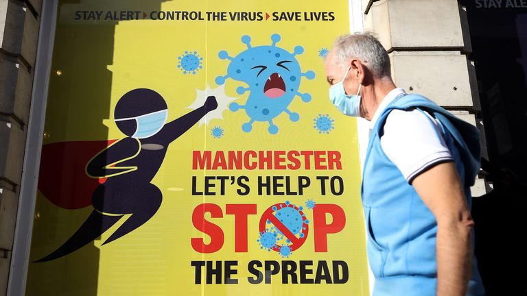 A person wearing a face mask walks past a Covid-19 sign on Deansgate in Manchester as the Government is preparing to impose stringent new coronavirus controls on 2.8 million people after talks with the local leaders for Greater Manchester failed to reach agreement. Leaders have been given until midday on Tuesday to reach a deal, or face unilateral Government action, after 10 days of negotiations failed to reach an agreement.