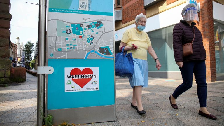 Women wearing a protective mask and a face shield walk past a city map, amid the coronavirus disease (COVID-19) outbreak, in Warrington, Britain September 22, 2020. REUTERS/Molly Darlington