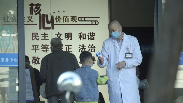 People are seen getting temperature checked before entering a hospital in Jiaxing, eastern China