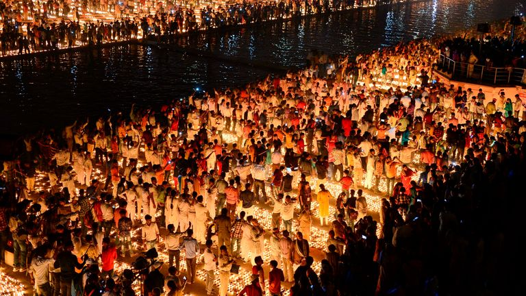 "TOPSHOT - Hindu devotees light earthen lamps on the banks of the River Sarayu on the eve of ""Diwali"" festival during an event organised by the Uttar Pradesh government, in Ayodhya on October 26, 2019. - ""Diwali"", the Festival of Lights, marks victory over evil and commemorates the time when Hindu god Lord Rama achieved victory over Ravana and returned to his kingdom Ayodhya. (Photo by SANJAY KANOJIA / AFP) (Photo by SANJAY KANOJIA/AFP via Getty Images)"