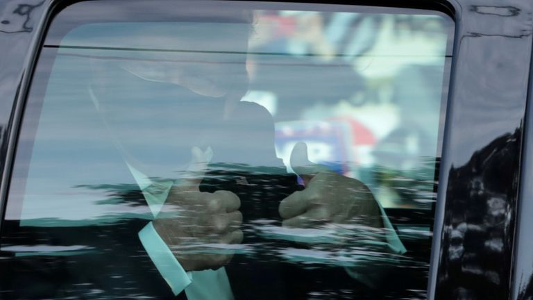Mr Trump gestures from the presidential car as he is driven outside the Walter Reed Medical Center