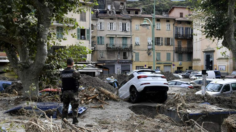 A gendarme stands amongst debris including vehicles in Breil-sur-Roya, south-eastern France, on October 4, 2020, after extensive flooding caused widespread damage in the Alpes-Maritimes departement.